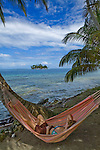 A woman relaxes in a hammock on Isla Pelikano, San Blas Islands, Kuna Yala, Panama
