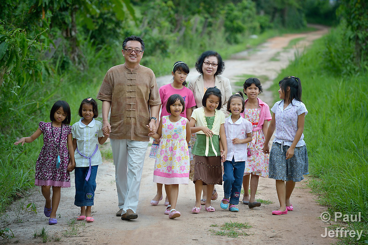 Gary and Cindy Moon, United Methodist missionaries in Thailand, walk with the girls who live in an orphanage they founded in Chiang Mai. The girls are orphans, and are all HIV positive.