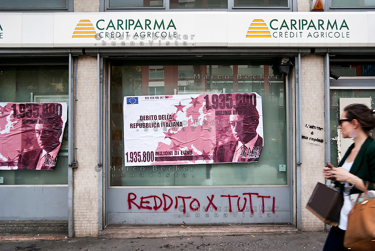 "Milano, ""Occupyamo Piazza Affari"", manifestazione di protesta di partiti e organizzazioni di estrema sinistra contro la crisi economica e i provvedimenti messi in atto dal governo. Un manifesto raffigurante una finta banconota del valore del debito pubblico italiano e con il volto del Presidente della Banca centrale europea Mario Draghi, affisso dai ragazzi di un centro sociale su una banca Cariparma --- Milan, ""Occupy Piazza Affari"", demonstration of  extreme left parties and organizations to protest against the  economic crisis and the Government. A poster of a fake bill of italian public debt value and with the face of European Central Bank President Mario Draghi, posted by some protesters of a social centre on a Cariparma Bank"