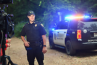 NWA Democrat-Gazette/CHARLIE KAIJO Capt. Chris Kelley with the Gravette police department prepares for a press conference, Friday, July 5, 2019 at a media staging area on the intersection of Crossover Rd and Gorden Hollow Rd in Gravette. <br /> <br /> Police responded to a shooting situation that left four people dead in an apparent murder suicide on a nearby property. All four people are related or lived at the residence. One body was found on the driveway. Authorities do not believe there is a danger to the public.