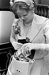 Filling brides handbag with confetti. Caxton Hall Westminster London. London's main register office until 1979. White wedding his and her uni sex clothes trouser suits flares or bell bottoms and cuban healed shoes. Long hair. 1970s fashionable London ..