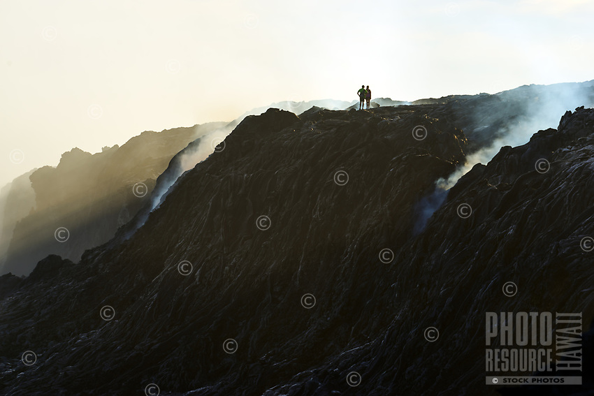 A couple stand on the edge of the dangerous Kamokuna cliffs near molten lava flow, Big Island of Hawai'i.