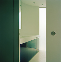 The bathroom is minimalist with a curving wall and sliding door.