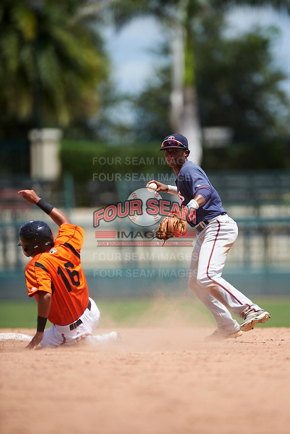 GCL Twins shortstop Gorge Munoz (2) throws to first as Jaime Estrada (16) slides into second during a game against the GCL Orioles on August 11, 2016 at the Ed Smith Stadium in Sarasota, Florida.  GCL Twins defeated GCL Orioles 4-3.  (Mike Janes/Four Seam Images)