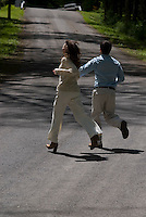 Man and woman running on country road