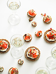 Elegant rounds of toast with soft cheese and smoked salmon lox, with glasses of champagne