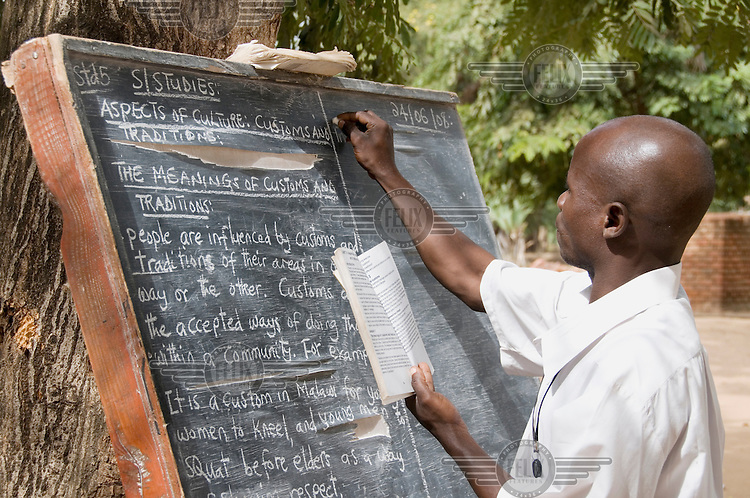 A man writes on a blackboard as he teaches social studies to a small class of pupils at a school supported by Mothercare (ActionAid partner).