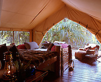 A fur-covered rustic bed with a daybed at its foot occupies a light and spacious tent with a wooden floor