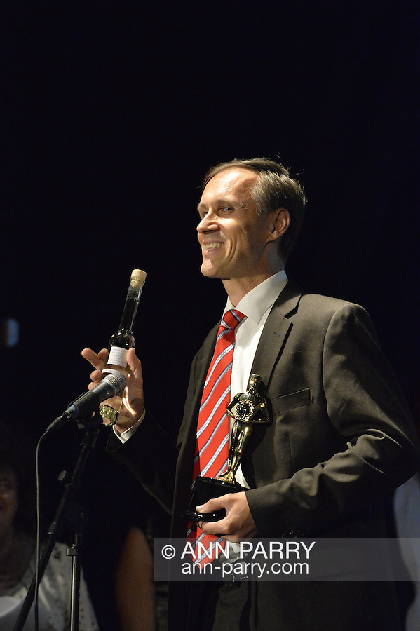 """Bellmore, New York, USA. July 21, 2016. BERNHARD RAMMERSTORFER accepts """"Alan Fortunoff Humanitarian Award"""" for documentary """"Taking the Stand"""" which he was director, producer and writer of, at The19th Annual Long Island International Film Expo Awards Ceremony, LIIFE 2016, held at the historic Bellmore Movies. Rammerstofer is holidng a bottle of Organic Austrian Schnaps Plum Self-Made by Ernst Blajs, a present he gave to LIIFE. LIIFE was called one of the 25 Coolest Film Festivals in the World by MovieMaker Magazine."""