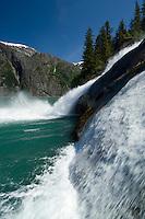 Waterfall cascades over rocks into aqua waters-Tracy Arm Fjord, Alaska, USA