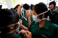Thai school children put masks on as they visit a hospice for those dying of AIDS at a Buddhist temple Wat Prabat Nampu, in Lopburi on the World AIDS day December 1, 2009. Thailand has been widely praised for its work in containing the virus. This remarkable achievement came about mainly because men used condoms more, and also reduced their use of brothels.  REUTERS/Damir Sagolj (THAILAND)