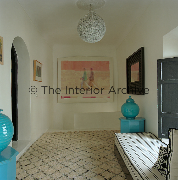 A pair of turquoise side tables and pots, a day bed by the window and a large rug make this top floor landing into a comfortable anteroom