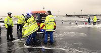 WEATHER PICTRURE WALES<br /> Pictured: Coastguard and police officers patrol the area to prevent people from going too near the edge of the marina wall as waves are crashing against it in Saundersfoot, Pembrokeshire, west Wales. Wednesday 05 February 2014<br /> Re: Severe weather experienced in parts of the UK due to strong winds and high tides. Severe flood warning have been issued by the Environment Agency.
