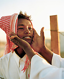 SAUDI ARABIA, Riyadh, a teenage boy works at a camel market in the desert outside of Riyadh