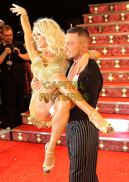 Kristina Rihanoff &amp; Robin Windsor <br /> The red carpet launch for 'Strictly Come Dancing' at Elstree Studios, Borehamwood, England.<br /> September 3rd, 2013<br /> full length gold dress black suit pinstripe trousers dancing arm in air lifting carrying holding half side profile <br /> CAP/FIN<br /> &copy;Steve Finn/Capital Pictures