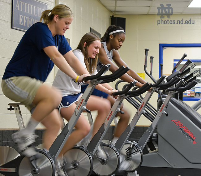Nov. 7, 2011; Women's Basketball players Brittany Mallory, left, and Deveraux Peters, right, work out on spin bikes with student Courtney Rauch...Photo by Matt Cashore/University of Notre Dame