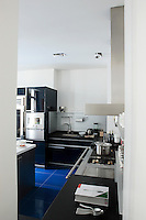 This high-tech, stylish blue and white kitchen is glimpsed through the open door