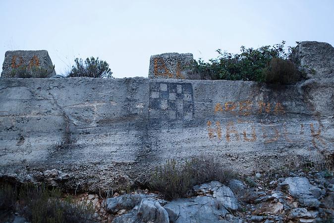 Eine stilisierte kroatische Flagge prangt auf einer Mauer in Neum, Bosnien-Herzegowina. Der kleine Ort Neum liegt in Bosnien-Herzegovina und bildet den einzigen Zugang zum Meer des Balkanlandes. Auf einer Länge von 9 km durchschneidet der Ort das kroatische Staatsgebiet (Neum-Korridor) Seit dem EU-Beitritt Kroatiens ist Neum auf beiden Seiten von EU-Außengrenzen eingeschlossen. /  A stylized Croatian flag on a wall in Neum, Bosnia and Herzegovina. The small city of Neum in Bosnia and Herzegovina is the only place in Bosnia, where the country has access to the adriatic sea. Over a length of 9 kilometers the area cuts Croatian territory in two pieces. Since Croatia became part of the European Union, the city of Neum is enclosed between two EU-boarders.