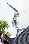 """Installation of a residential wind turbine is filmed for an episode of the DIY network show """"This New House"""". Bob Hayes of Prevailing Winds and his crew install a Dyocore SolAir 800 I wind turbine which integrates two small solar panels into its design and is capable of producing up to 800 Watts at 12 mph. The two solar panels produce up to 45watts. Redondo Beach, Ca, USA"""