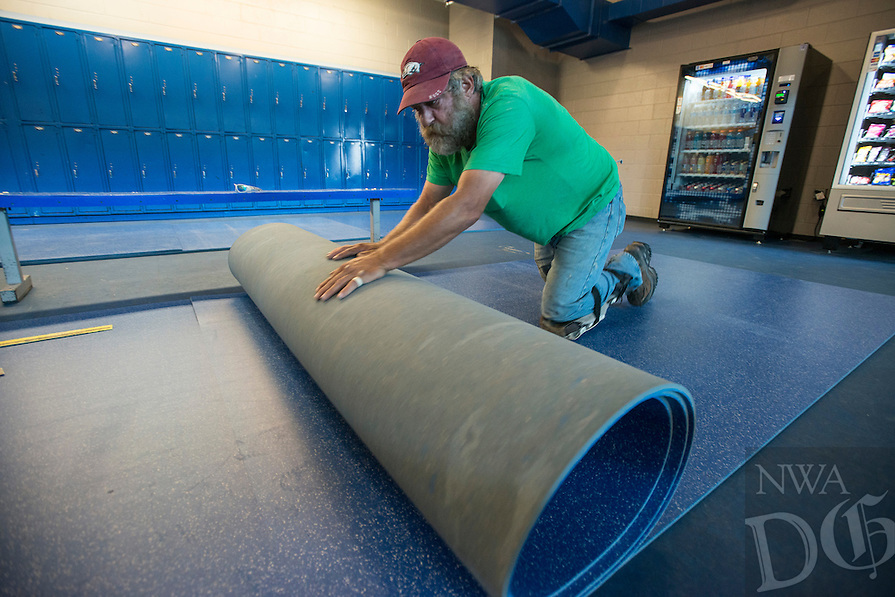 STAFF PHOTO ANTHONY REYES &bull; @NWATONYR<br /> Thell Oaks, with Miller Commercial Flooring, rolls up a cut piece of rubber flooring Thursday, Aug. 21, 2014 for the Jones Center ice rink in Springdale. A section of the floor will be replaced near the counter and door to the ice rink. Oaks figured the heavy duty 10 foot by six foot section of floor he was cutting weighed close to 300 pounds.