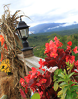 Stock photo: lamp post and decorated flower plants on a wooden fence looking over clouded smoky mountain hills from a distance.