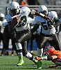 Joshua Milfort St. Cyr #23 of Elmont breaks a tackle an rushes for a gain during the Nassau County varsity football Conference II semifinals against Carey at Hofstra University on Saturday, Nov. 12, 2016. Carey won by a score of 33-24.