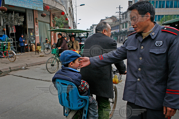A soldier touches the face of a child riding on the back of a bicycle on a street.