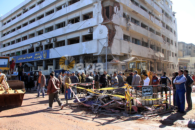 Egyptians inspect destruction in the Egyptian city of Mansura, North of Cairo, following a powerful car bomb explosion on December 24, 2013. The bombing tore through a police building in Mansura early today, killing at least 14 people, an attack the authorities said was aimed at derailing the country's transition to democracy. Photo by Mohammed Bendari