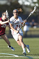 Boston College midfielder Caroline Margolis (21) on the attack as Harvard University midfielder Audrey Todd (21) defends.