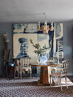 In the dining room, an antique chandelier hangs above a Syrian table. The bleach-on-denim painting and chairs are by Robshaw