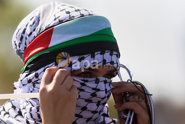 A female Palestinian protester clashes with Israeli security forces near the Beit El settlement on the outskirts of Ramallah in the West Bank, on October 17, 2015. The unrest that has engulfed Jerusalem and the occupied West Bank, the most serious in years, has claimed the lives of 34 Palestinians and seven Israelis. The tension has been triggered in part by Palestinians' anger over what they see as increased Jewish encroachment on Jerusalem's al-Aqsa mosque compound. Photo by Shadi Hatem