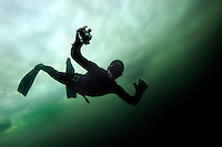 Terje Brandshaug freediving under the ice while taking pictures with a digital camera. Lutvann lake, outside Oslo, Norway. Photo: Fredrik Naumann/Felix Features