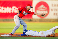 Malcolm Holland (5) of the Ogden Raptors slides head first into second base between the legs of Jarrod Parks (9) of the Orem Owlz at Lindquist Field on July 27, 2012 in Ogden, Utah.  The Raptors defeated the Owlz 6-3.   (Brian Westerholt/Four Seam Images)