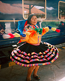 PERU, Cusco, South America, Latin America, mature woman in traditional clothing performing in front of the Hiram Bingham Train. The train travels from Cusco to Aguas Calientes and back.