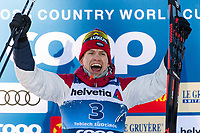 1st January 2020, Toblach, South Tyrol , Italy;  Alexander Bolshunov of Russia celebrates on the podium after the mens 15 km classic technique pursuit during Tour de Ski on January 1, 2020 in Toblach.