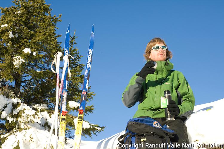 Mann drikker te fra termos på skitur. ---- Man drinkin tea on skiing trip.