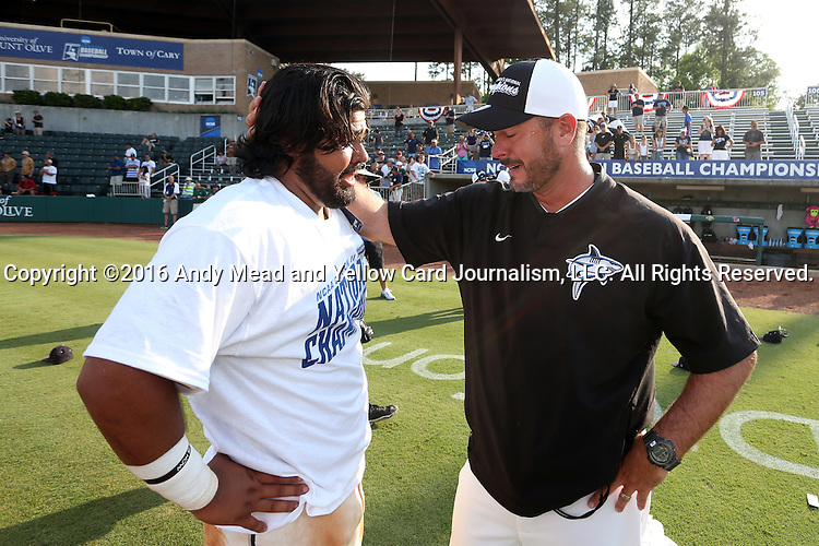 04 June 2016: Nova Southeastern head coach Greg Brown (right) shares a moment with Andres Visbal (left). The Nova Southeastern University Sharks played the Millersville University Marauders in Game 14 of the 2016 NCAA Division II College World Series  at Coleman Field at the USA Baseball National Training Complex in Cary, North Carolina. Nova Southeastern won the game 8-6 and clinched the NCAA Division II Baseball Championship.