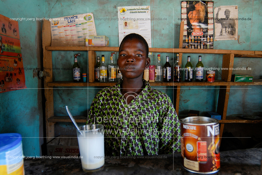 BURKINA FASO , boy sell Nescafe and Pastis liquor in country bar in village, image of national hero Thomas Sankara beside pin-up calenda at the wall /<br /> Bar in einem Dorf, Verkauf von Nescafe und Pastis Schnaps