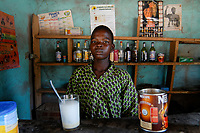 BURKINA FASO , boy sell Nescafe and Pastis liquor in country bar in village, image of national hero Thomas Sankara beside pin-up calenda at the wall /<br /> Bar in einem Dorf, Verkauf von Nescafe und Pastis Schnaps