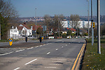 Swansea, UK, 25th March 2020.<br />The usually busy main road that runs from Mumbles to Swansea is completely deserted this afternoon during the Coronavirus lockdown. Singleton Hospital can be seen in the distance.