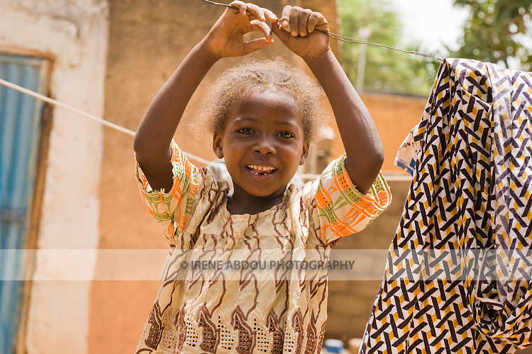 In Ouagadougou, Burkina Faso, a young Fulani girl plays on the laundry line in her family's compound.