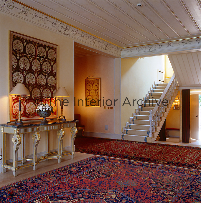 Red and blue Turkish rugs and wall hangings bring an opulent exoticism to the entrance hall of this yali in Istanbul