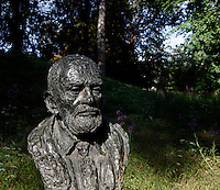 Low angle view of the bust statue of Theodore Monod seen in the morning light, created by Nacera Kainou in 2001 and located at the bottom of the Labyrinth in the Jardin des Plantes, Paris, 5th arrondissement, France. Nacera Kainou is French contemporary sculptor and painter who was chosen by the Museum National d'Histoire Naturelle to create the statue as a memorial to Theodore Monod at his death in 2000. Founded in 1626 by Guy de La Brosse, Louis XIII's physician, the Jardin des Plantes, originally known as the Jardin du Roi, opened to the public in 1640. It became the Museum National d'Histoire Naturelle in 1793 during the French Revolution. Picture by Manuel Cohen