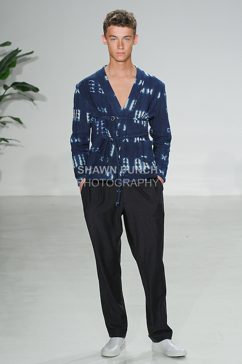 Model walks runway in a double tie African mud cloth noragi and side tab navy trouser, from the Palmiers du Mal Spring Summer 2017 collection by Brandon Capps and Shane Fonner, at Skylight Clarkson Square on July 14 2016, during New York Fashion Week Men's Spring Summer 2017.