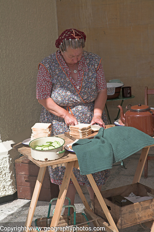Living History event. Woman in 1940s clothing making sandwiches for tea.