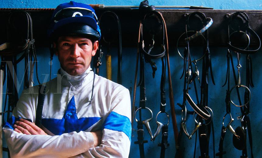 Portrait of a jockey in tackroom setting.