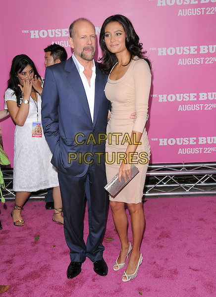 "BRUCE WILLIS & EMMA HEMING .The Columbia Pictures' Premiere of ""House Bunny"" held at The Mann Village Theatre in Westwood, California, USA..August 20th, 2008.full length blue suit jacket hand in pocket beige dress arm around waist silver clutch bag couple .CAP/DVS.©Debbie VanStory/Capital Pictures."