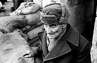 LETTLAND, 27.03.91.Riga.Waehrend des anhaltenden Kampfes um die Unabhaengigkeit ist die Stadt immer wieder marodierenden sowjetischen Sondertruppen ausgesetzt, an Schluesselpunkten stehen daher Barrikaden. - Alter Mann im Eingang des Radiogebaeudes am Domplatz in der Altstadt. (Es ist Rudolfs Reinhards, 1907-1993, der einmal in der Telefonzentrale des Radios gearbeitet hatte.) | During the ongoing fight for independence the town is regularely raided by Soviet special forces. Key spots are therefore protected by barricades. - Old man standing in the entrance of the radio central at the central cathedral square..© Martin Fejer/EST&OST.