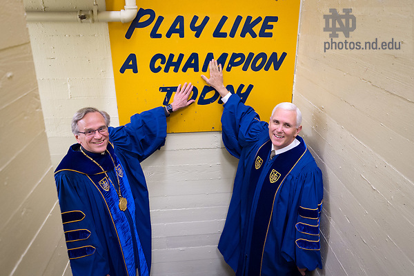 """May 21, 2017; University of Notre Dame President Rev. John I. Jenkins, C.S.C. and Vice President Mike Pence touch the """"Play Like A Champion Today"""" sign in the football locker room before Commencement 2017. Vice President Pence received an honorary degree and was the Commencement speaker at the ceremony. (Photo by Matt Cashore/University of Notre Dame)"""