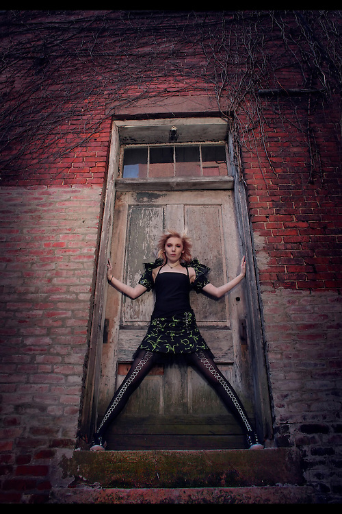 A young woman standing with legs apart in a doorway of an old redbrick building
